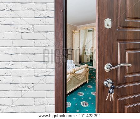 Half opened door to a bedroom, handle closeup. Welcome, privacy concept. Entrance to the hotel suit, modern interior design.