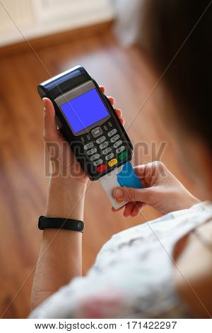 Hand putting plastic card into credit card terminal at merchant paying for sale. Screen template.