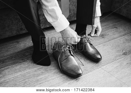 Black and white art photography monochrome man wears shoes. Tie the laces on the shoes. Men's style. Professions. To prepare for work to the meeting.