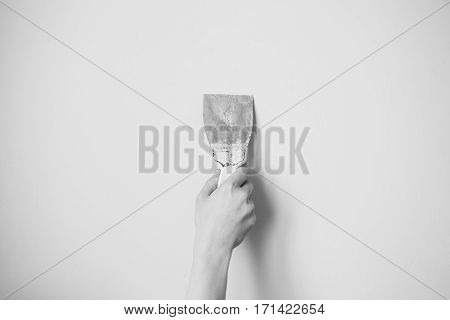 Black and white art photography monochrome trowel in man's hand on a background of a white wall. Dirty tools for repair. Tool for getting rid of the wallpaper. Space for text