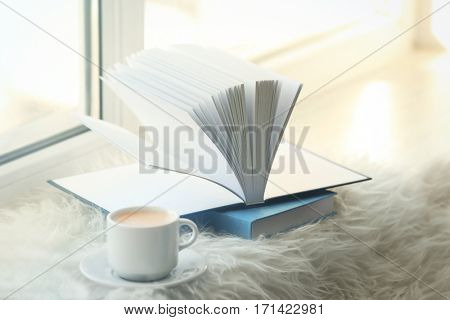 Cup of coffee and books on windowsill