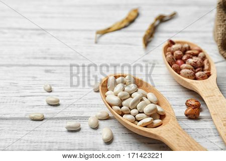 Assortment of haricot beans in spoons on white  wooden background