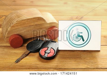 Car key, toy and card with handicap sign on wooden background