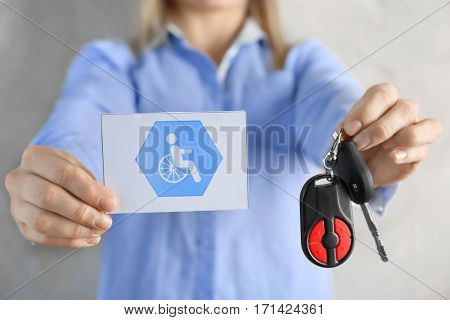 Woman holding car key and card with handicap sign, closeup