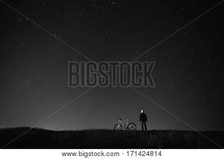 black and white art photography monochrome starry sky night photography astrophotography the silhouette of a man a man standing next to a mountain bike on the background of a starry sky