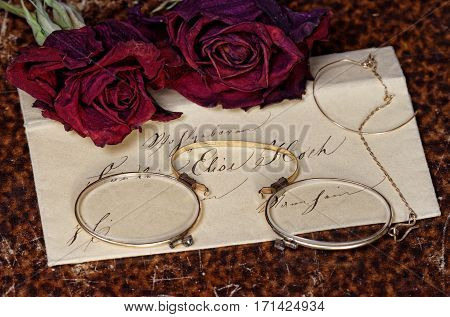 Nostalgic Reading Corner Concept: concept of a vintage reading desk with historic envelope, old book cover background, historic female glasses and dried red roses