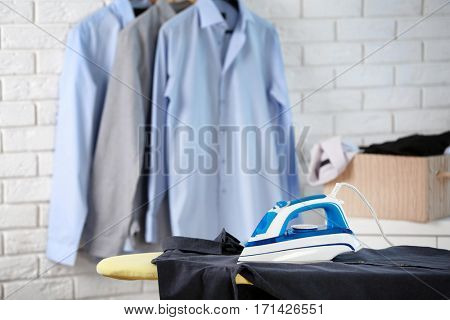 Modern iron and clothes in dry-cleaning salon