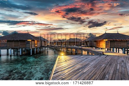 Colorful sunset over Maldivian wooden, water villas