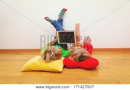 little boy and girl looking at touch pad relaxed at home, home comfort