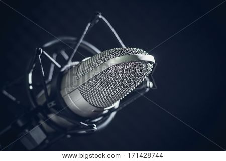 Microphone and audio console in holder isolated on dark background in recording studio. Toned image