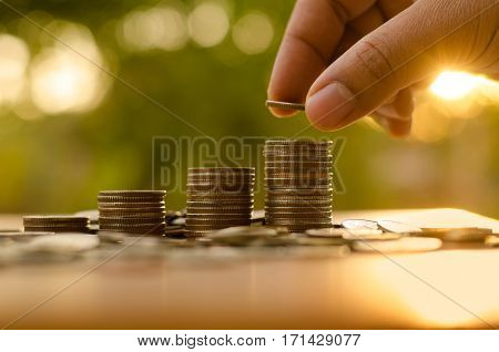 business man putting money coins like growing graph with sun light in saving money and investor insurance concept over green background
