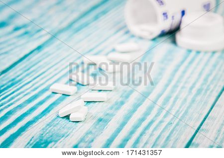 White Tablets And Bottle For Tablets On Blue Background.free Space For Text.