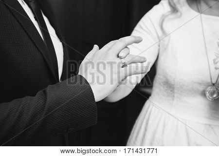 Black and white art photography monochrome wedding rings on hands of bride and groom. Couple in love. Dress wedding bands.