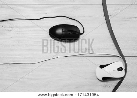 Black and white art photography monochrome Interactive race on speed between white and black computer mouse on wooden background. Input device for cursor control.