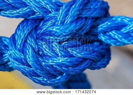 Shipping objects concept. Blue strong sailing ropes tied with knot. Outdoor shot on sunny day.