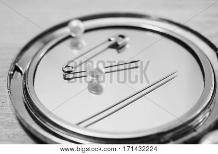 Black and white art photography monochrome double mirror pins needles and sewing items white beads on a light wooden background work of seamstresses
