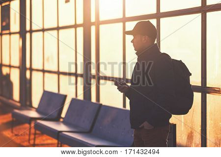 Young traveler with mobile phone in hand waiting at the bus station during sunset.