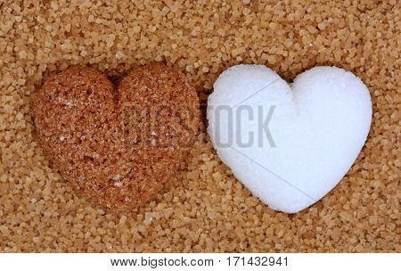 Beige sugar heart with white sugar heart on sugar background closeup