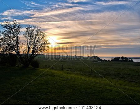 Beautiful landscape of green fields and a dramatic majestic sunset great nature background