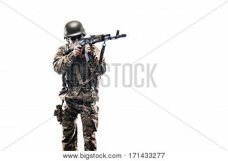 Studio shot of young serviceman in uniform holding machine gun and aiming on white background. Isolate.