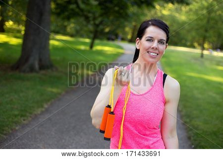 healthy girl in the park holding a skipping rope