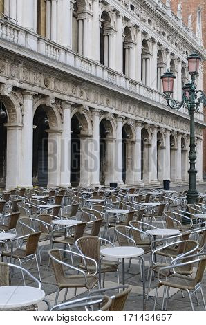 Early morning in Venice. Empty cafe tables and chairs in San Marco Square Venice Veneto Italy Europe