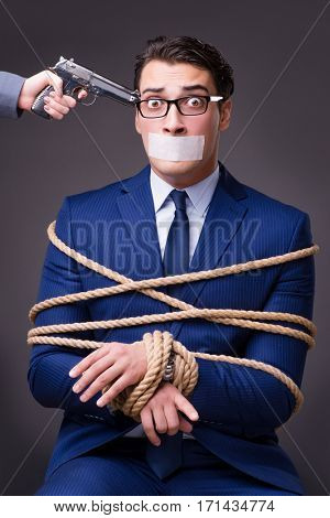 Businessman taken hostage and tied up with rope