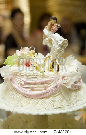 Decoration on wedding cake figurine of the bride and groom on the cake.