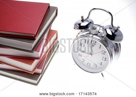 Pile of books and clock over white