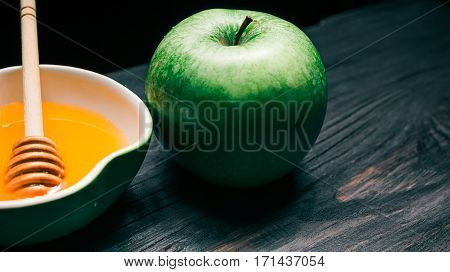 Fresh green apple next to apple-shaped bowl of honey with dipper. Selective focus