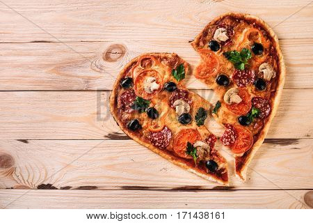 heartbreak shaped pizza with tomatoes and mozzarella for Valentines Day on vintage black background. Food concept of romantic love.
