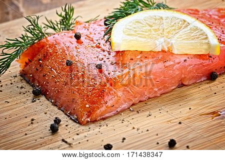 salmon fish with fresh herbs, pepper and lemon