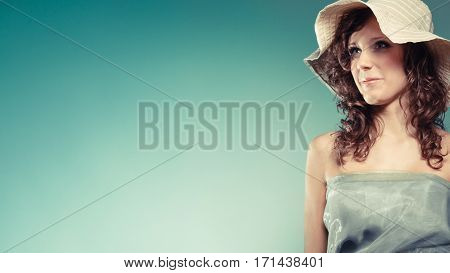 Fashion cosmetics and summertime. Modern young woman with light green dress and summer hat.