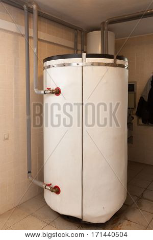 A domestic household boiler room with a new modern solid fuel boiler heating electric warm water system and pipes