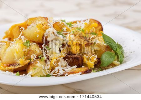 Fries with smashed eggs and parmesan with herbs on white plate