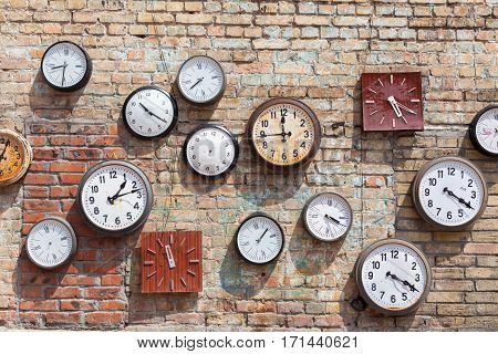 Brick wall background with numerous round and square clocks