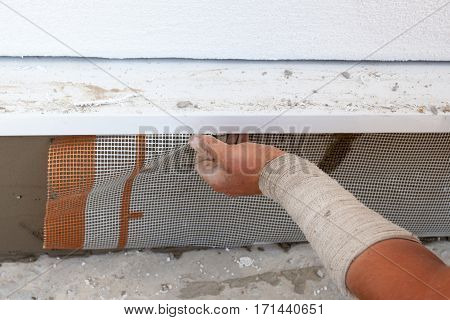 Man hand installing mesh over plastering foundation