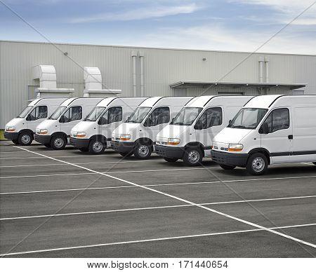 Photograph of white vans fleet in blue sky parking lot.
