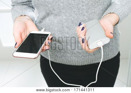 Two Girls Hands Hold Of The Phone And Charger. Powerbank And Smartphone In Girl's Hands.