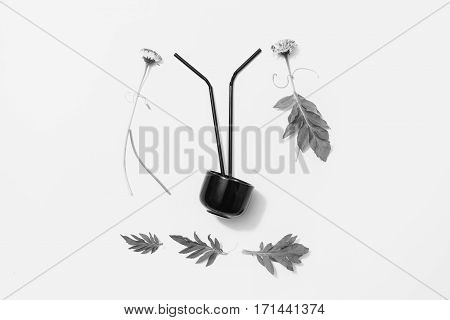 Black and white art photography monochrome flower patern on a white background. Silhouette of man and woman of flowers. Black mug with a cocktail stick.
