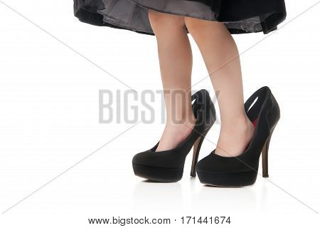 Childs feet in a big green shoes with heels on a white background