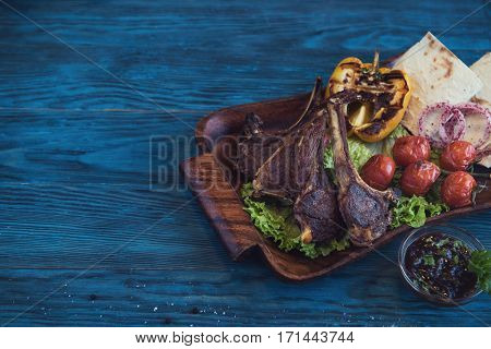 Grilled lamb meat with vegetable on a blue wooden background
