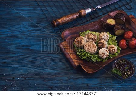 Grilled mushrooms champignons with vegetable on a blue wooden background