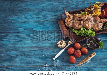 Grilled quail meat with vegetable on a blue wooden background