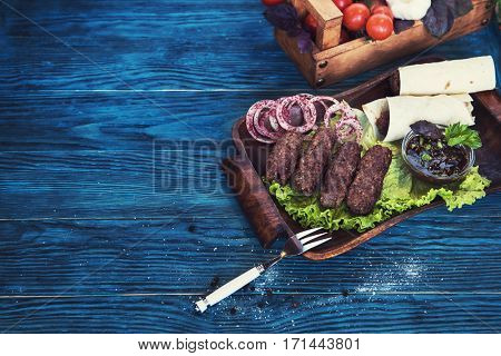 Grilled lula kebab - meat dish, with vegetable on a blue wooden background
