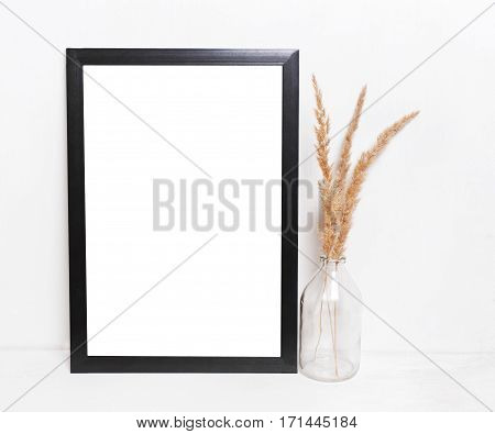 Blank black picture frames on on white background with the decor of dry twigs and glass vases. Mockup in hipster style workspace