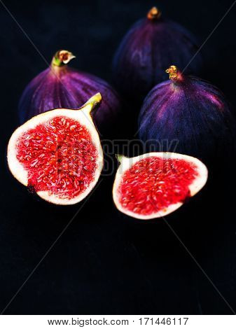 Ripe sweet figs on black background. Healthy Fresh fig fruit vivid colors.