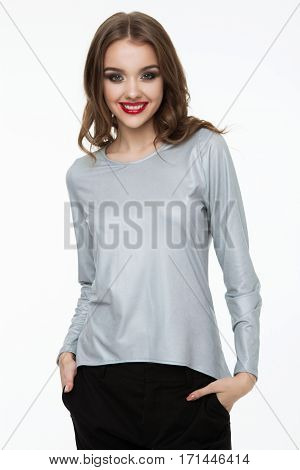 Beautiful fashion model wearing silver grey top and black pants on white background