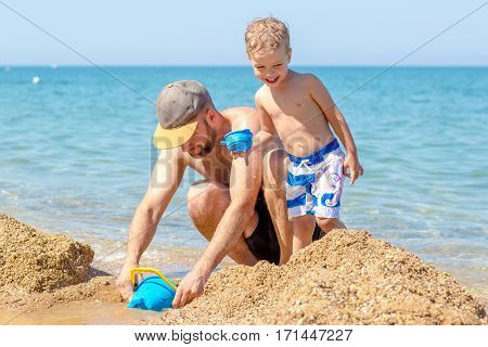 Dad and little son playing together on the sea