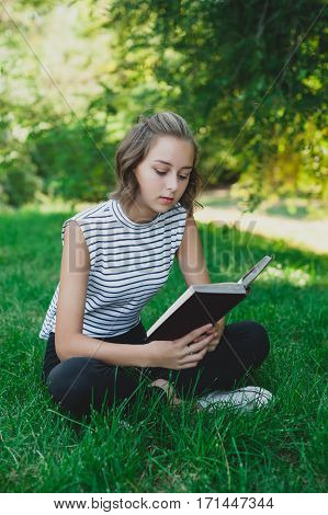 Teen girl reading book in the park.